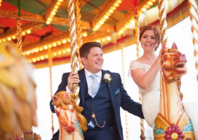 Wedding photography at Preston Court in Canterbury - bride & groom on fairground ride