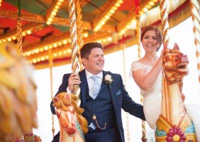 Wedding photography at Preston Court in Canterbury - bride & groom on fairground ride